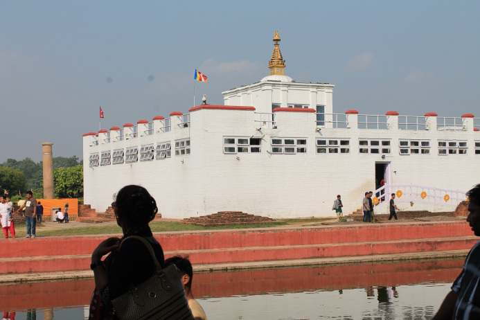 Landscape with a a river and a big white building with red details. There is many windows in the building and a big gold tower on the roof. People are walking around the building and the river.