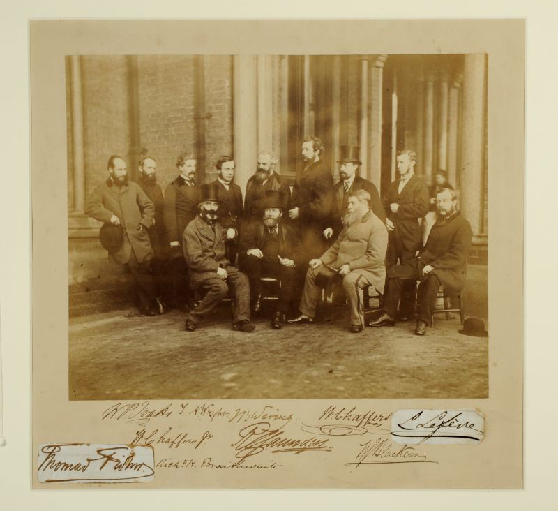 a Black and white photograph of lots of old men sitting on stools to have their photograph taken outside the infirmary. Most of them are wearing hats.