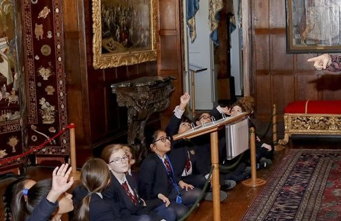 School children are sat on the floor, listening to a learning officer.