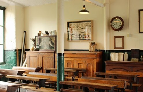 View of a Victorian classroom with wooden desks and traditional furniture