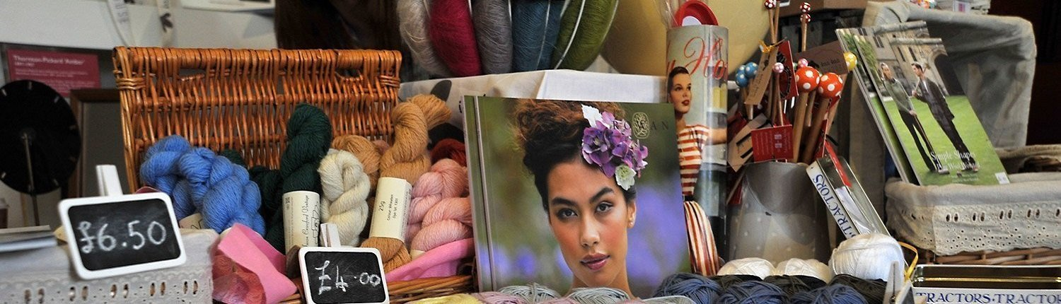 Wool yarns and knots, a book with a woman's face on, magazines, photographs and tins