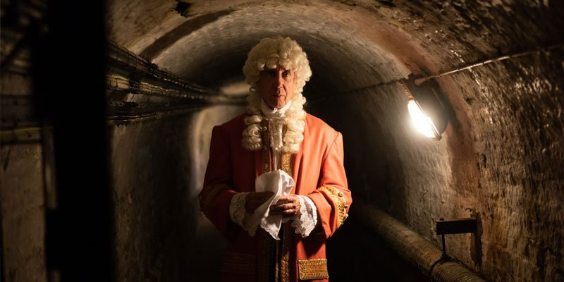 A man is dressed in Georgian clothing, and standing in a dark cellar.