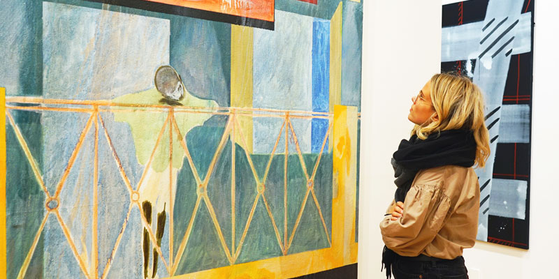 A girl looking at a piece of brightly painted contemporary art hung up on a wall