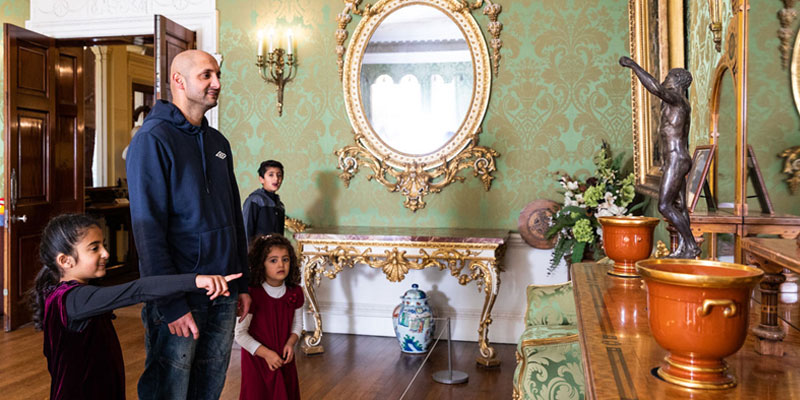 A family looking at some of the furniture in the drawing room of Lotherton hall