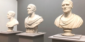 Three classical stone made busts sitting on plinths in an art gallery
