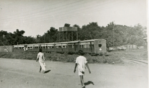 a black and white photograph of two people walking towards a train.