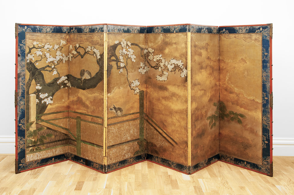 A folding screen in gold with a picture of a cheery blossom against the background of a golden sky.