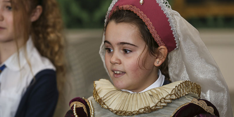 A young girl is dressed in traditional Tudor costume including head wear and a ruff